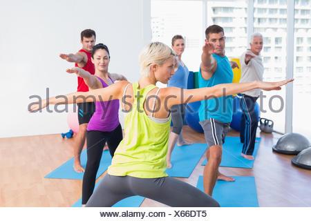 Des gens pratiquant guerrier de poser dans les fitness club Banque D'Images