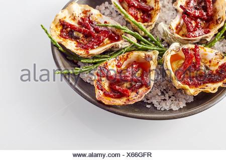Close Up Still Life sur une assiette d'Huîtres Kilpatrick préparé avec du bacon et du fromage et servi sur fond blanc avec copie Espace Banque D'Images