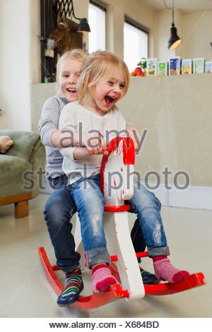 Deux jeunes sœurs jouant sur cheval à bascule Banque D'Images