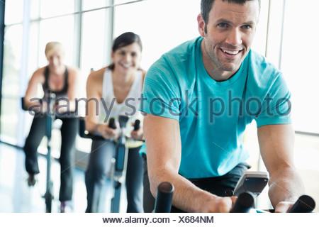 Les personnes qui usent sur vélos stationnaires en classe de conditionnement physique Banque D'Images