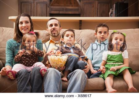 Vue avant de la famille avec enfants (18 à 23 mois, 4-5, 6-7, 8-9) sitting on couch watching TV and eating popcorn Banque D'Images