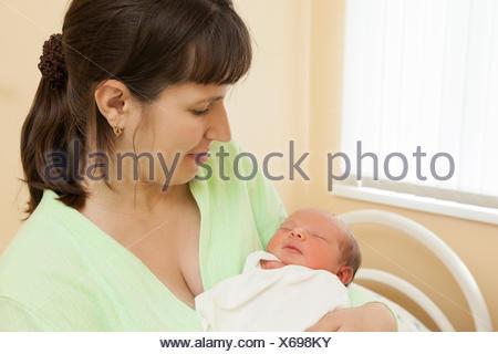Dormir mignon bébé nouveau-né sur les mains de la mère de l'enfant Banque D'Images