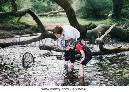 Une femme donnant un garçon un piggyback et tenant un filet de pêche de patauger dans un ruisseau peu profond. Banque D'Images