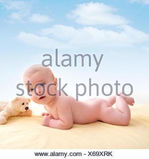Bond petit bébé yeux bleus couché smiling on bed jaune clair. Banque D'Images