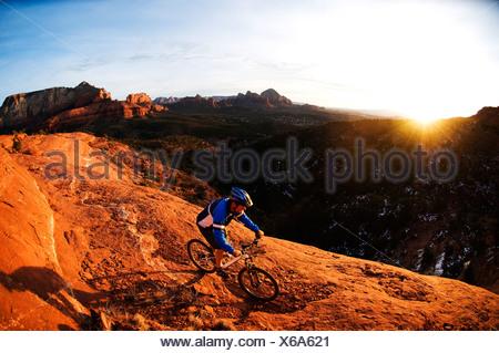 Un homme d'âge moyen chevauche son vtt à travers le red rock country autour de Sedona, Az au coucher du soleil. Banque D'Images