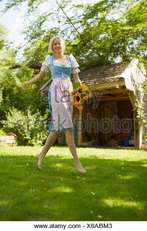 Femme portant des fleurs dans jardin Banque D'Images