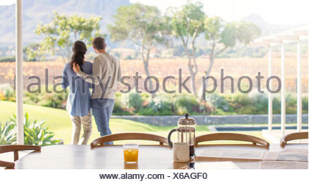 Couple hugging on patio donnant sur terrain Banque D'Images