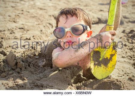 Portrait d'un garçon enterré dans le sable sur la plage Banque D'Images