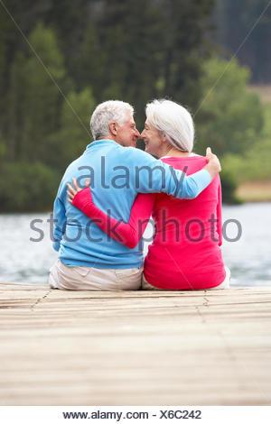 Romantic senior couple assis sur une jetée Banque D'Images