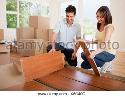 Couple unpacking box in new house Banque D'Images