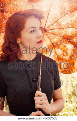 La Suède, Redheaded woman holding umbrella Banque D'Images