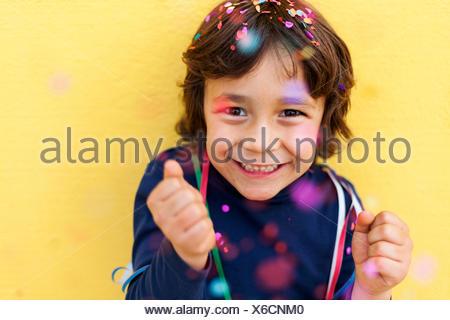 Happy little boy standing in front of mur jaune tandis que les confettis tombant sur lui Banque D'Images