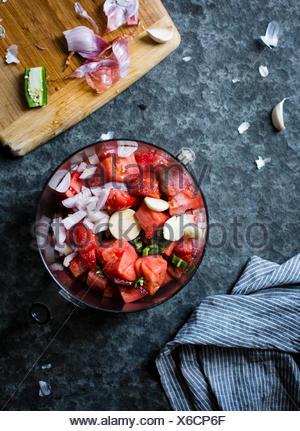 La tomate et l'oignon haché dans un mélangeur. Banque D'Images