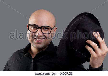 Homme chauve décoller son chapeau Banque D'Images