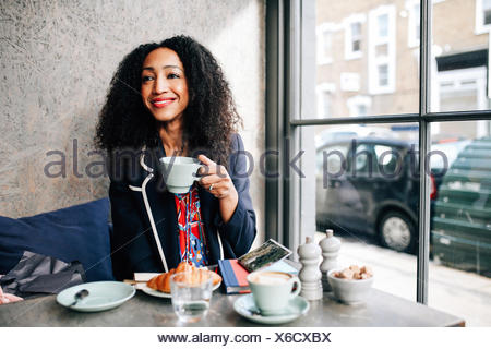 Mid adult woman holding Coffee cup in cafe Banque D'Images