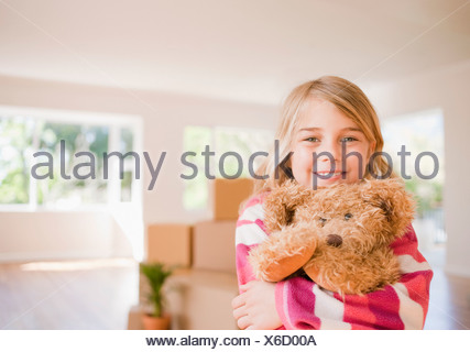 Girl hugging teddy bear in new house Banque D'Images