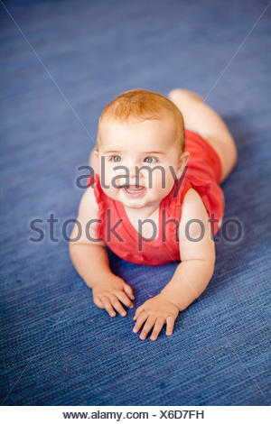 Portrait of a smiling baby girl lying on floor Banque D'Images
