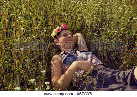 Young woman lying in prairie avec des fleurs dans ses cheveux Banque D'Images