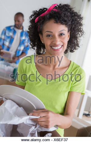 Mid adult woman unwrapping plate, man in background Banque D'Images