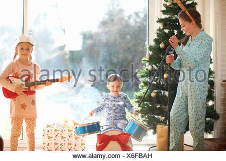 Garçon et sœurs jouer jouet kit de batterie et guitare le jour de Noël Banque D'Images