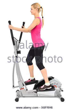 Jeune femme faisant des exercices sur l'entraîneur elliptique Banque D'Images