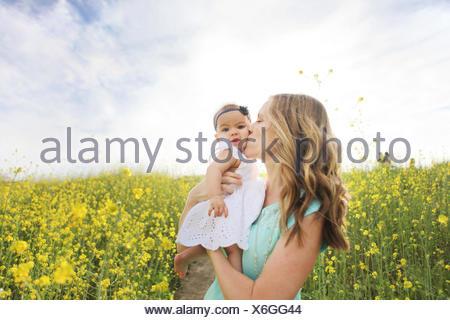 Mère embrassant bébé fille dans le champ de fleurs Banque D'Images