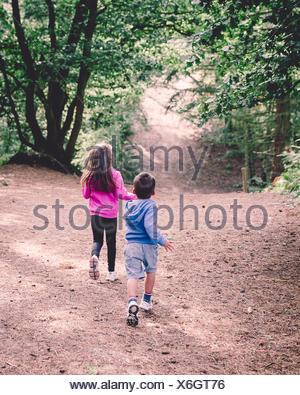 Vue arrière de deux enfants qui courent dans les bois Banque D'Images