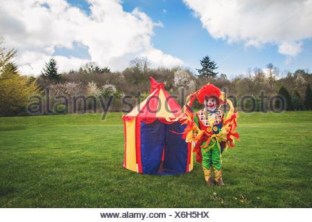 Garçon habillé comme un clown debout devant une tente de cirque de jouet Banque D'Images