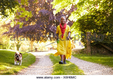 Portrait of Senior Woman Walking Dog Pet In Countryside