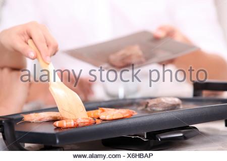 La cuisson des crevettes sur une table top cuisinière Banque D'Images