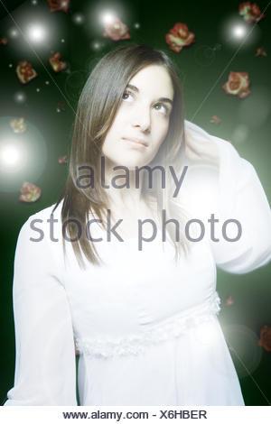 Femme, jeune, hier et d'oeil, demi-portrait, blur, lumières, fleurs, gens, portrait de femme, cheveux longs, brune, fairytale, magique, conte de fées, magie, rêve, désir, studio, à l'intérieur, rêveur, robe, blanc . Banque D'Images