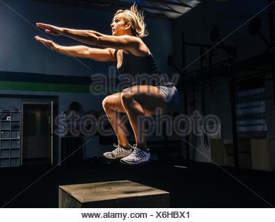 Young woman jumping mid air sur sport fort avec les bras atteignent dehors Banque D'Images