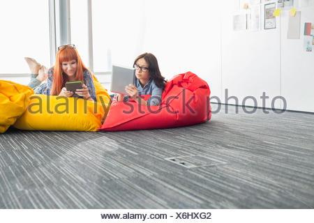 L'utilisation de tablettes numériques d'affaires tout en vous relaxant sur les chaises de pouf dans creative office Banque D'Images