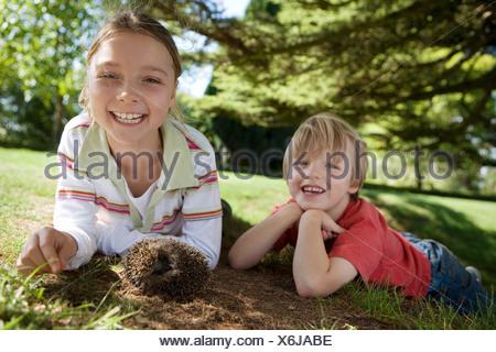 Garçon et fille 6 4 7 9 bloody mary dans jardin à côté de hedgehog smiling portrait d'inclinaison au niveau de la surface Banque D'Images