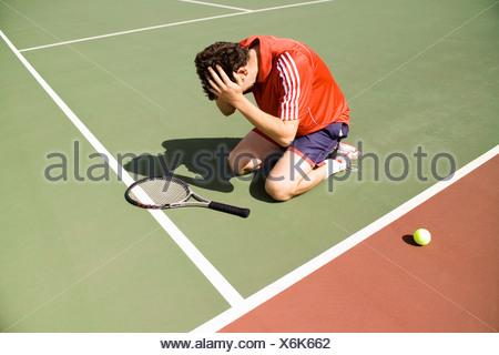 Un joueur de tennis à genoux sur la cour dans la défaite Banque D'Images