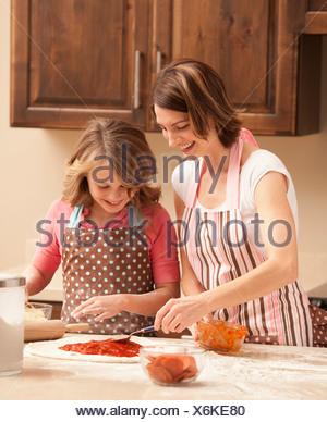 USA, Utah, Léhi, Mère et fille (10-11) la préparation de pizza dans la cuisine Banque D'Images