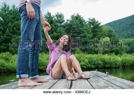 Un couple sur une jetée en bois par un lac. Banque D'Images