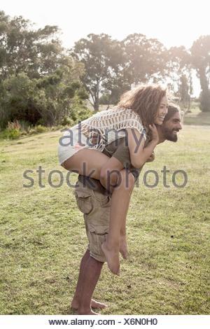 Vue latérale du jeune homme se pencher vers l'avant donnant aux jeunes woman piggyback smiling Banque D'Images