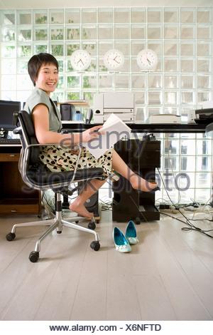 Les jeunes pieds nus woman holding, paperasse, smiling, portrait Banque D'Images