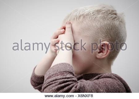 Portrait of boy wearing brown cavalier, couvrant le visage avec les mains Banque D'Images