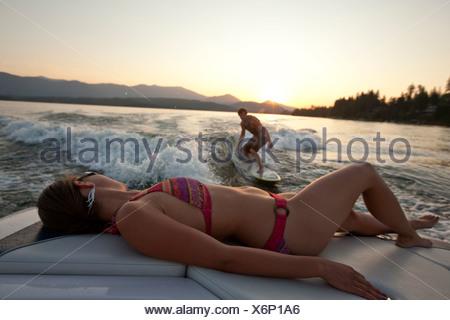 Jeune homme wakesurf dans New York comme une fille en bikini montres du bateau. Banque D'Images