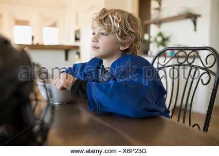 Pensive boy eating cereal at table Banque D'Images