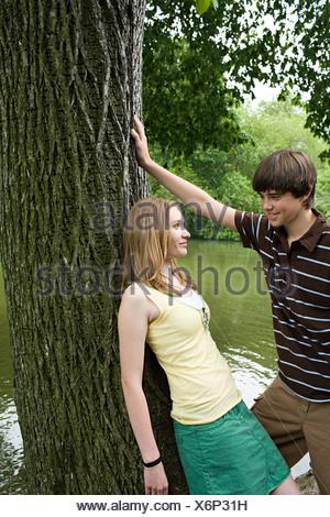 Teenage couple flirting près d'un arbre Banque D'Images