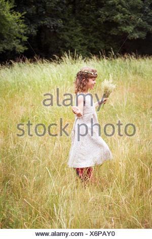 Jeune fille avec des fleurs dans ses cheveux cueillette des fleurs dans un pré. Banque D'Images