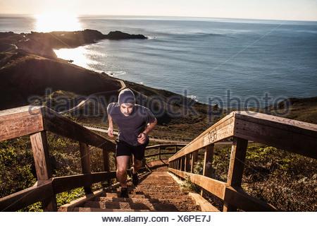 Jeune homme courir vers le haut escalier côtières au coucher du soleil Banque D'Images