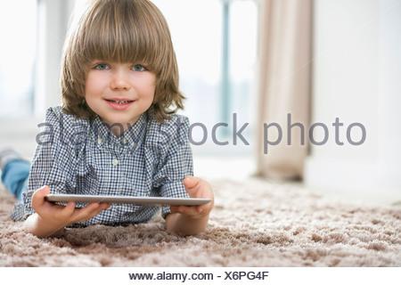 Portrait of happy boy with digital tablet allongé sur un tapis à la maison Banque D'Images