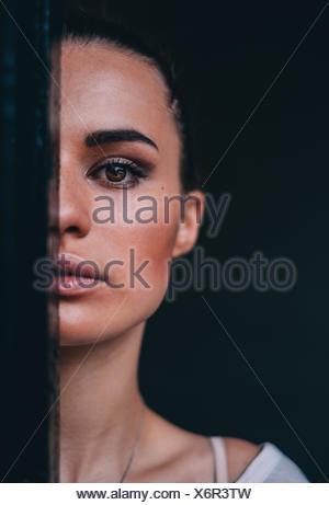 Portrait d'une belle femme se cacher la moitié de visage derrière un rideau Banque D'Images