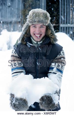 Jeune homme dans la neige smiling Banque D'Images
