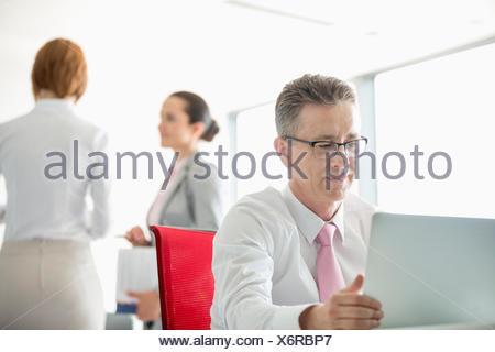 Businessman using laptop avec des collègues discutant en arrière-plan à l'office de tourisme Banque D'Images