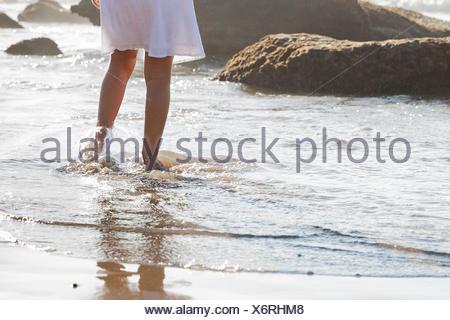 Fille qui marche dans les vagues sur la plage Banque D'Images